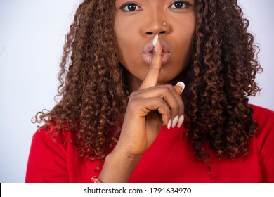 closeup of young african woman with her finger over her mouth gesturing for silence