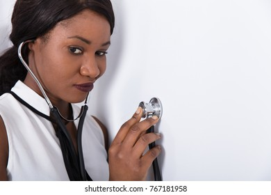 Close-up Of A Young African Woman Placing Stethoscope On Wall