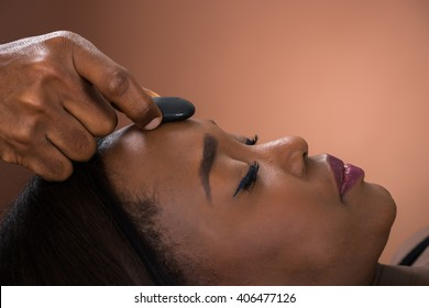 Close-up Of Young African Woman Receiving Hot Stone Massage At Spa