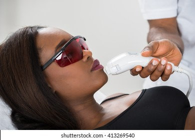 Close-up Of Young African Woman Receiving Epilation Laser Treatment On Face