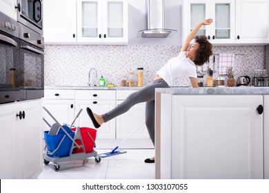 Close-up Of A Young African Woman Slipping While Mopping Floor In The Kitchen