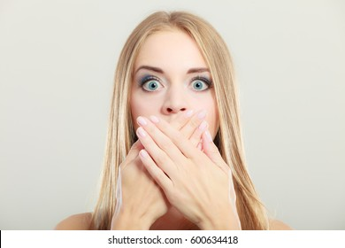 Closeup young amazed woman wide eyed covering her mouth with hands on gray