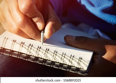 Closeup of young american african man making notes in copybook. Male student writing new ideas at paper pad