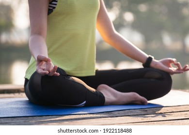 Closeup of a young Asian beautiful woman practicing yoga and meditate in the lotus pose outdoor beside the lake in the morning for relaxation and peace of mind. Harmony and meditation concept.