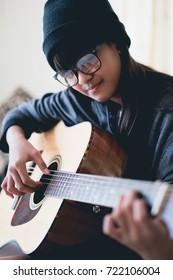 Closeup young asian girl play acoustic guitar