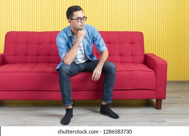 Close-up of young Asian handsome bearded man, wearing eyeglasses in denim shirt, sitting on red sofa, serious face, hands clasp under chin, in modern living room, bright yellow stripe wall background