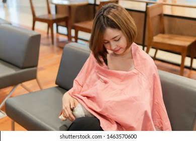 Closeup young asian mother is breastfeeding her newborn baby and using nursing breastfeeding cover in a cafe while she is having coffee time.