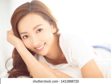 closeup young asian smiling woman on bed