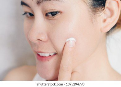 Closeup of young Asian woman applying moisturizer cream on her face. Conceptual of beauty and skin care.