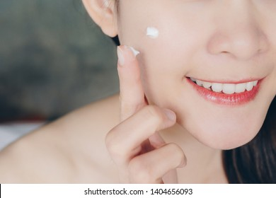 Closeup of young Asian woman applying acne cream/moisturizer on her face. Conceptual of beauty and cosmetic.
