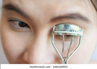 Closeup of young Asian woman using eyelash curler. Eyelash curler is a hand-operated mechanical device for curling eyelashes for cosmetic purposes.