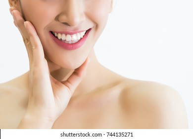 Closeup of young attractive woman with healthy teeth laughing with her hands on her face over white background