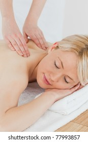 Closeup of young attractive woman receiving a back massage in a spa center