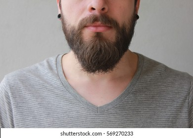 Close-up of young bearded man standing against grey background, perfect beard.