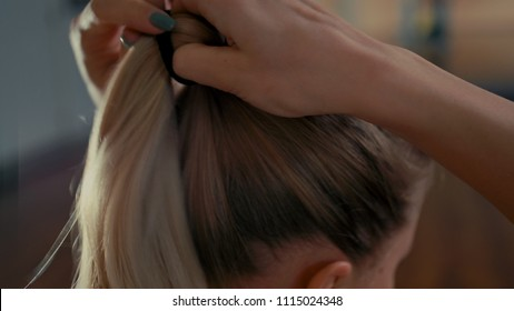CloseUp of Young Beautiful Blond Woman Tying her Hair and Making Ponytail while Preparing for Training in the Gym