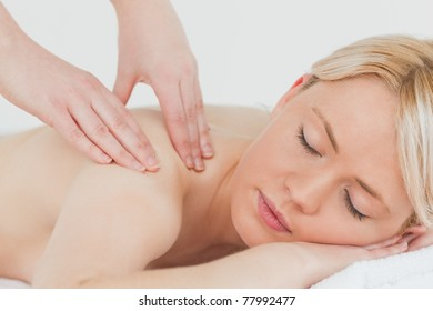 Closeup of young beautiful blonde woman receiving a back massage in a spa centre
