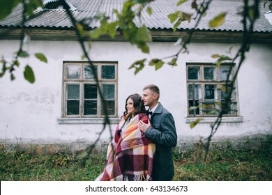 Closeup of young beautiful couple embracing under blanket in a cold day near the old building