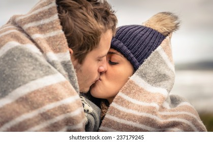 Closeup of young beautiful couple kissing under blanket in a cold day with sea and dark cloudy sky on the background