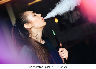Close-up of young, beautiful girl Smoking hookah in the club. Sexy woman exhales smoke.