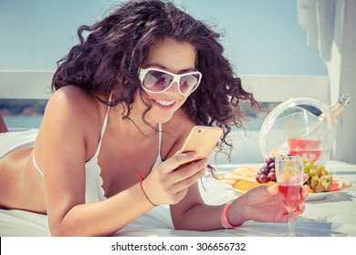 Closeup young beautiful happy, excited smiling woman texting, looking on mobile cell phone isolated outdoors on sun-bed at sea, lake background. Positive face expression human emotion, feelings.