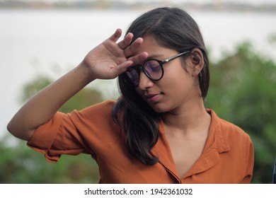 Closeup of a young beautiful Indian girl looking sidewise, Women in stress | wearing glasses | fashion and lifestyle | Girl touching her forehead to check fever at outdoor