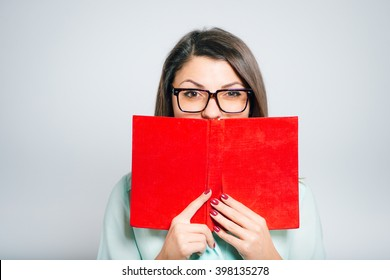 closeup of a young beautiful woman hiding behind the book with glasses
