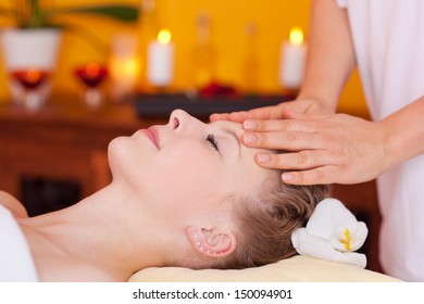 Closeup of young beautiful woman receiving head massage treatment at a wellness center