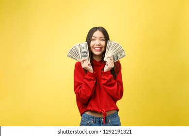Closeup of young beautiful woman with us dollar money in hand over yellow background, with copy space