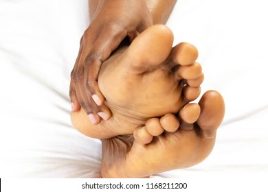 Closeup of Young black African American woman suffering from Podalgia at home with selective focus on hand massaging foot