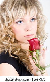 Close-up of the young blond girl face with a rose