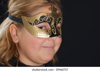 Closeup of a young blonde girl wearing a venetian mask, shot against a black background