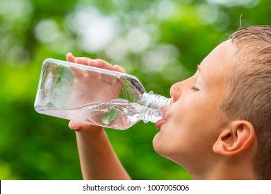 Closeup of young boy drinking pure tap water from transparent plastic drinking bottle while outdoors on a hot summer day.