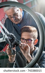 close-up of a young boy face adjusting his bicycle's derailleur under the expert eye of his grandfather
