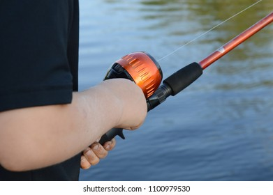 Closeup of a young boy fishing with his rod and reel.