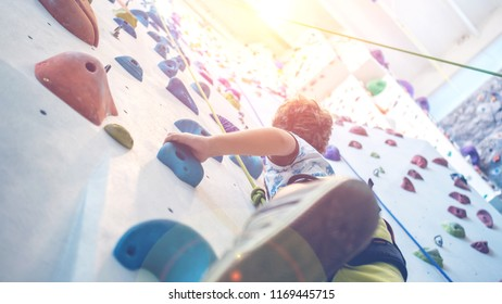 closeup of young boy hanging on a rope leading to the top of an artificial climbing wall, personal development and career growth or challenge yourself concept