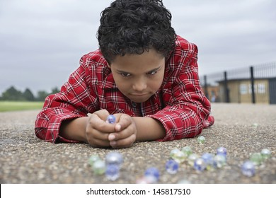 Closeup of young boy playing marbles on playground