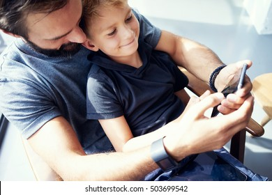 Closeup of young boy sitting with father and using mobile phone in modern sunny place. Horizontal, blurred background
