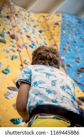 closeup of young boy watching a rope leading to the top of an artificial climbing wall, personal development and career growth or challenge yourself concept