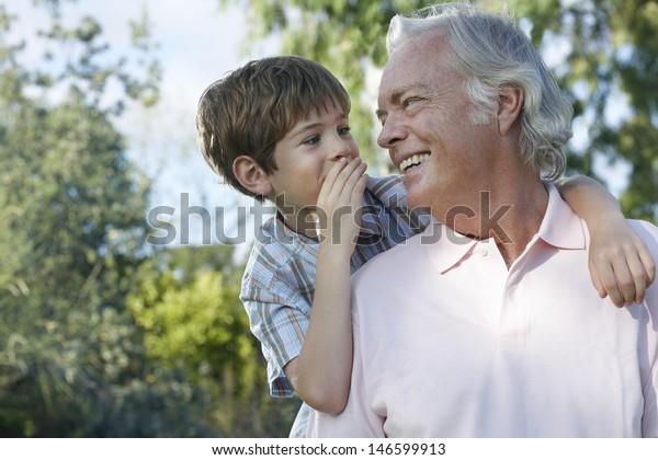 Nahaufnahme eines jungen Jungen, der im Ohr des Großvaters im Freien flüstert