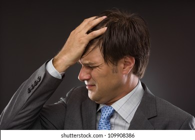 Closeup of young business man with headache on gray
