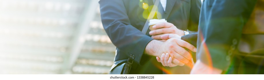 Closeup young business man shaking hands with cup of coffee in street city outdoors. Teamwork friendship businessman entrepreneur partnership  greeting brainstorm success synergy communication concept