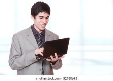 Closeup of a young business man standing with a laptop  in a light and mordern background.