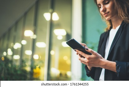 Close-up young business woman chatting mobile phone with colleagues on social media on background office lighting lights, women's hands using smartphone outdoors, lifestyle and communication concepts