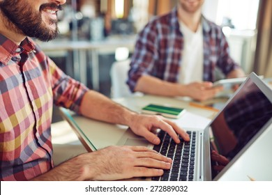 Close-up of young businessman computing in office