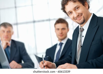 Closeup of a young businessman with his colleagues at the background.