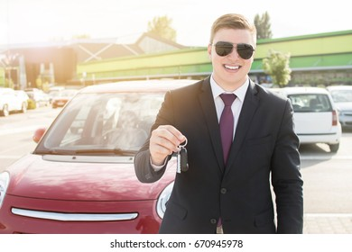 Close-up of a young businessman holding car keys. Brand new car. Man smiling while holding car keys.