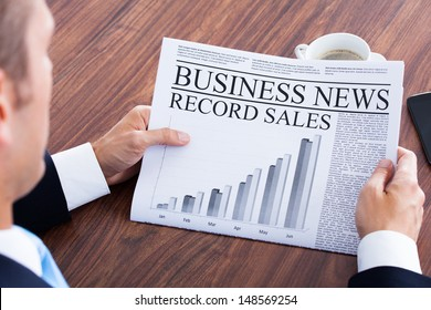 Close-up Of Young Businessman Reading News On Newspaper