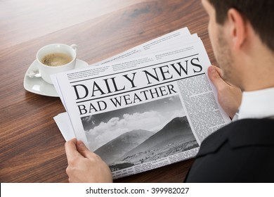 Close-up Of Young Businessman Reading Weather News On Newspaper