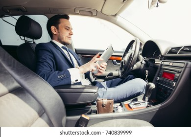 closeup of a young businessman using a tablet in a car