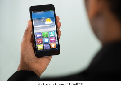 Close-up Of Young Businesswoman Holding Mobile Phone With Multicolored App